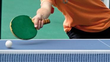 Image d'une élève jouant au ping pong, plan sur la raquette touchant la balle